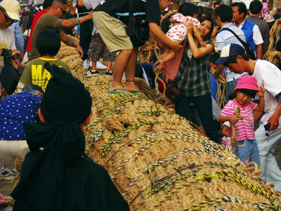 People scramble to cut a piece of the rope