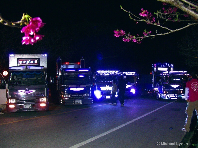Decorated trucks illuminate the Cherry Blossoms at night