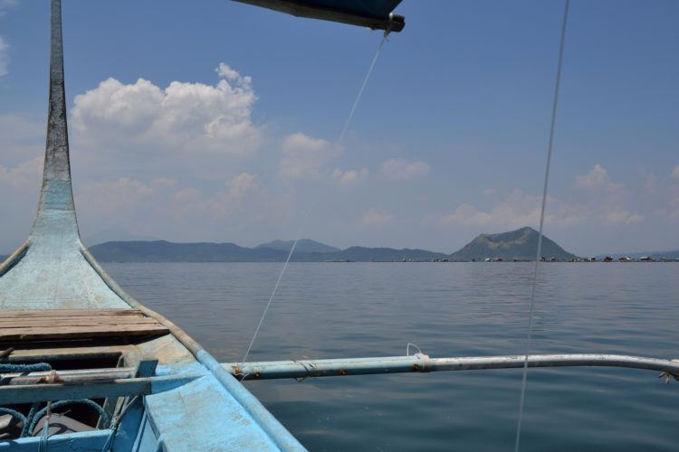 Filipino boat with Mount Taal Volcano island in the distance