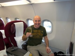 Drinking a glass of pre-flight champagne in business class on Qatar Airways