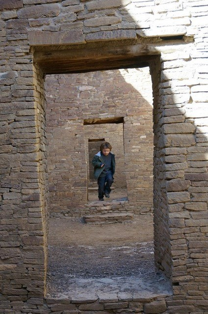 A boy running the doorways in the ruins of Chaco Canyon.