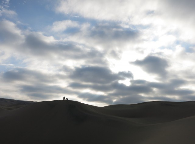 Two travelers stand atop one of the dunes and discuss the descent they're about to make.