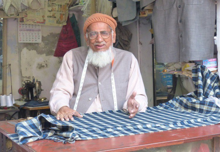 An Indian tailor, hard at work. Image source.