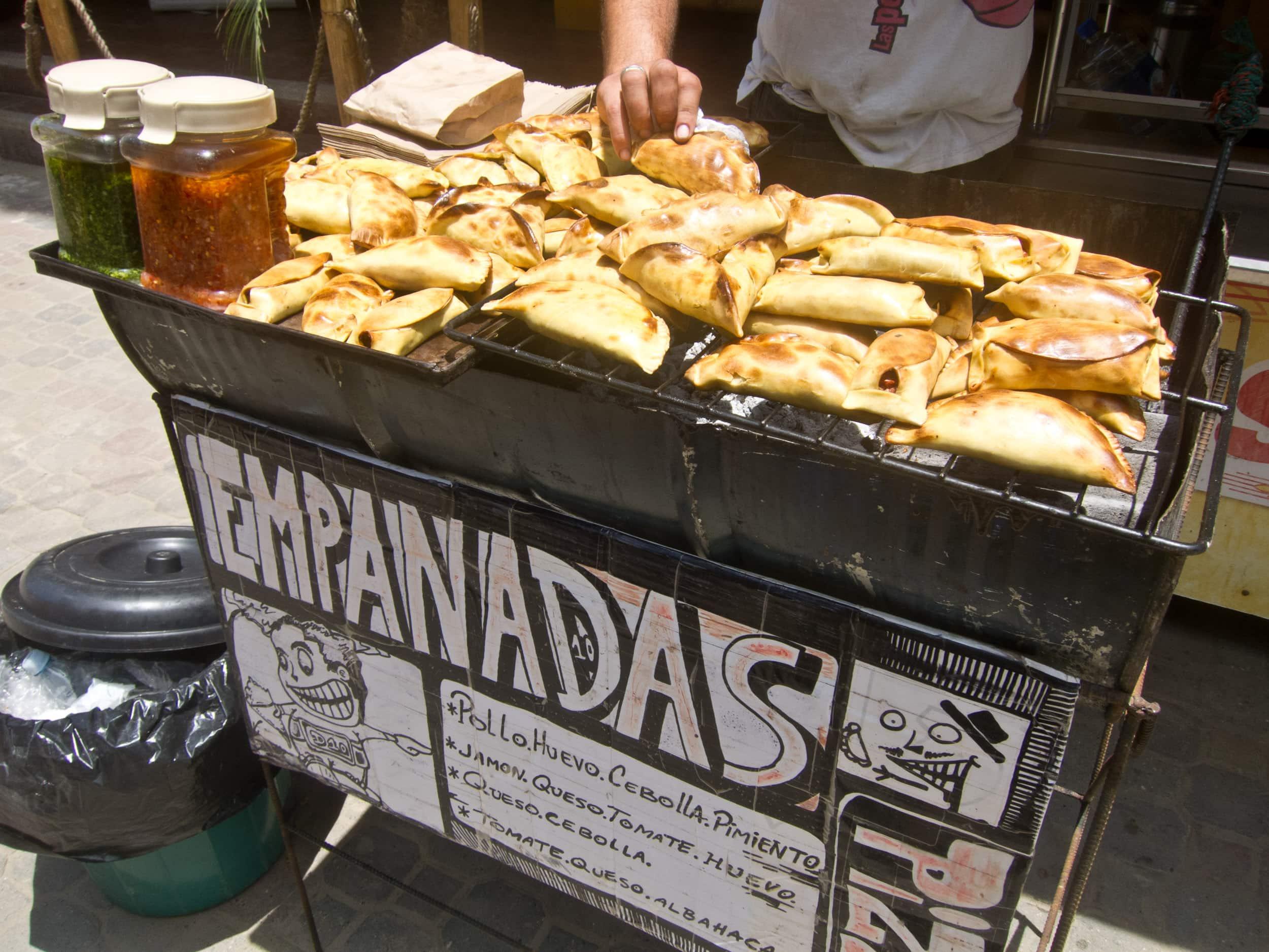 An Argentinian sells empanadas for $1 apiece on the street