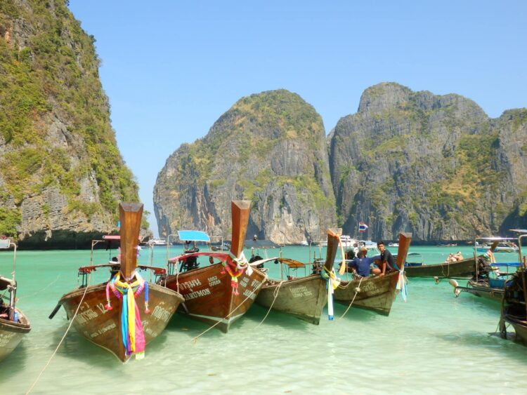 Longboats in Maya Bay, Thailand before it was closed due to overtourism
