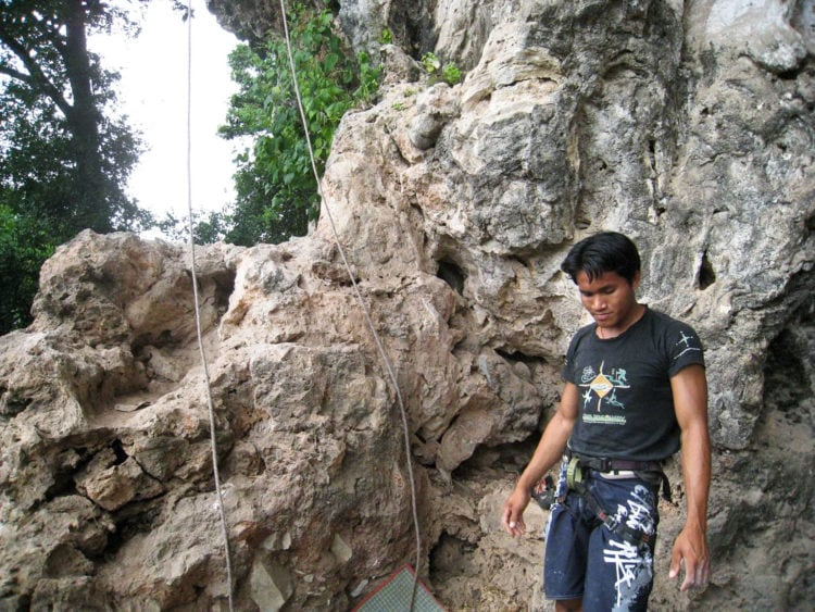 A rock climbing guide in Laos prepares to belay me