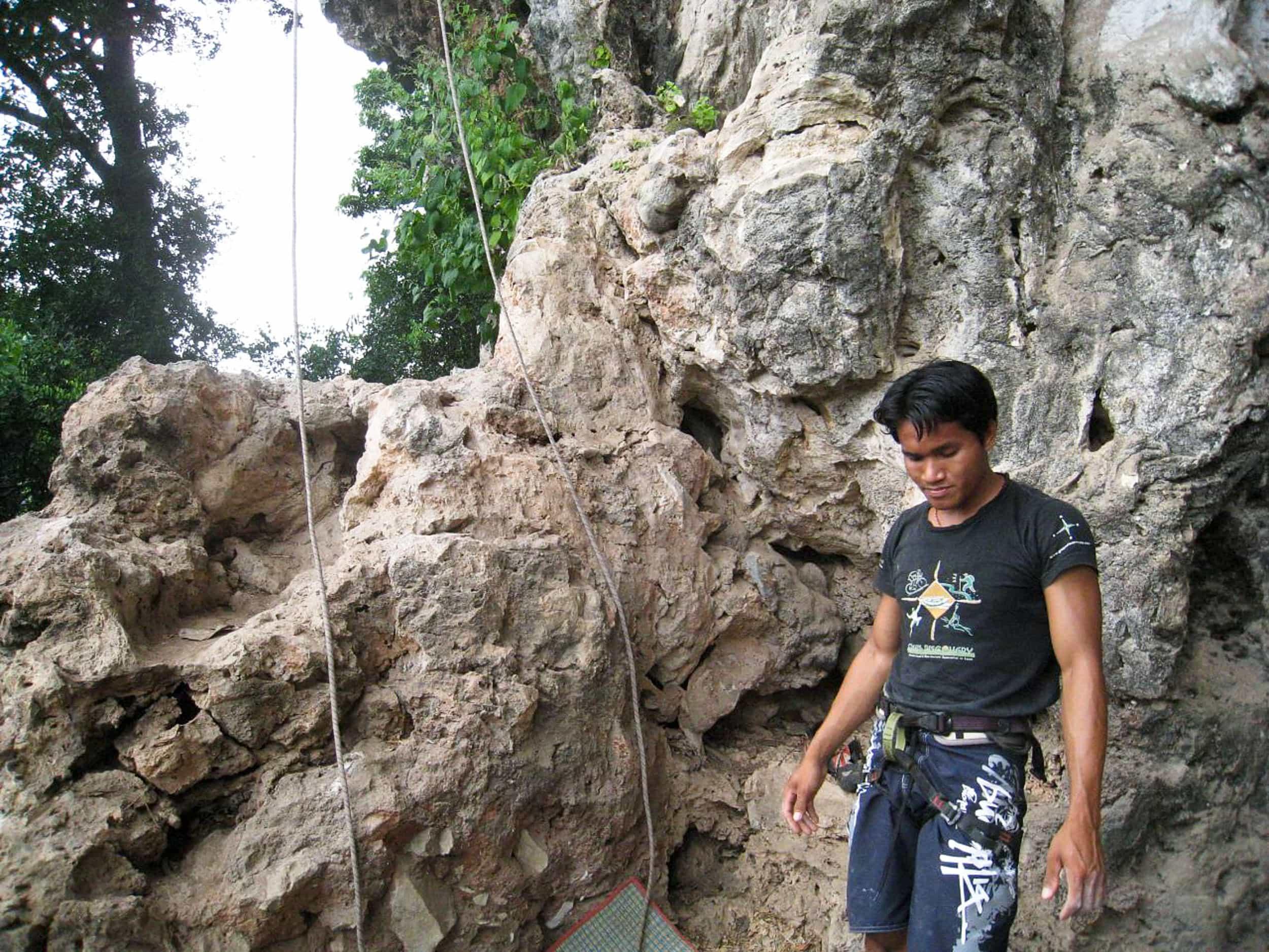 A rock climbing guide in Laos prepares to belay me