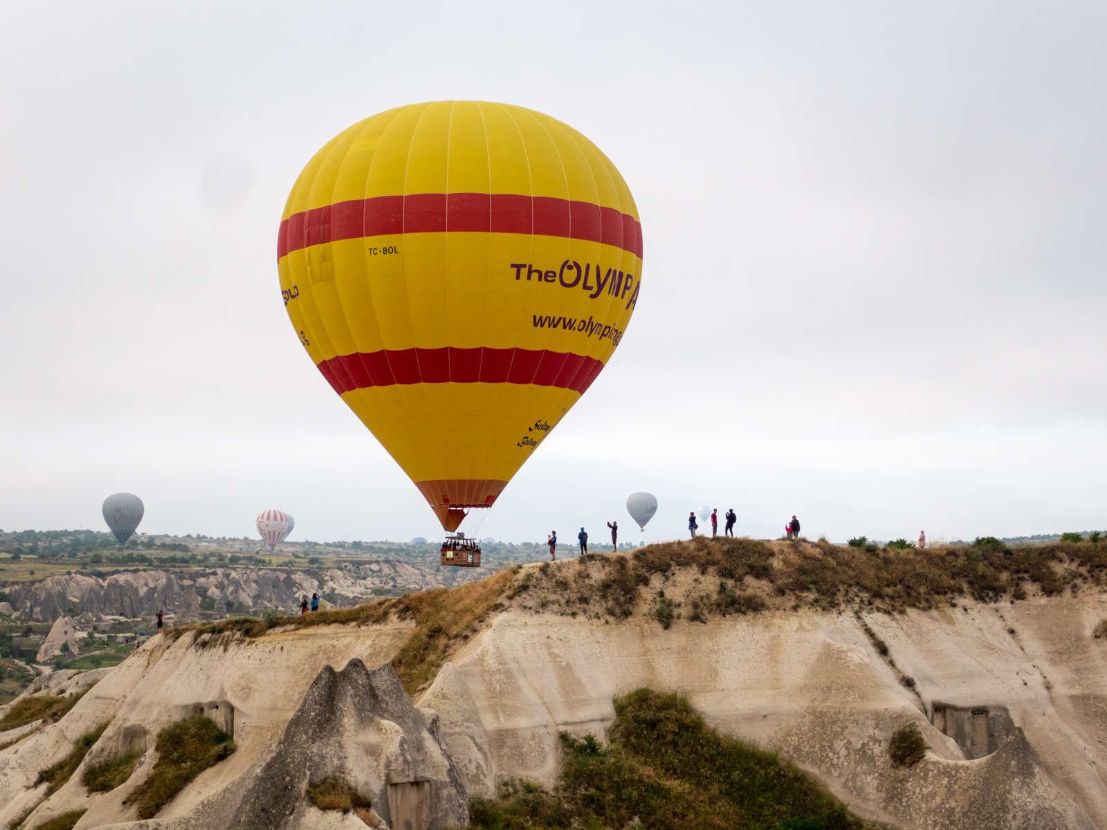 A hot air balloon passes a scenic outlook
