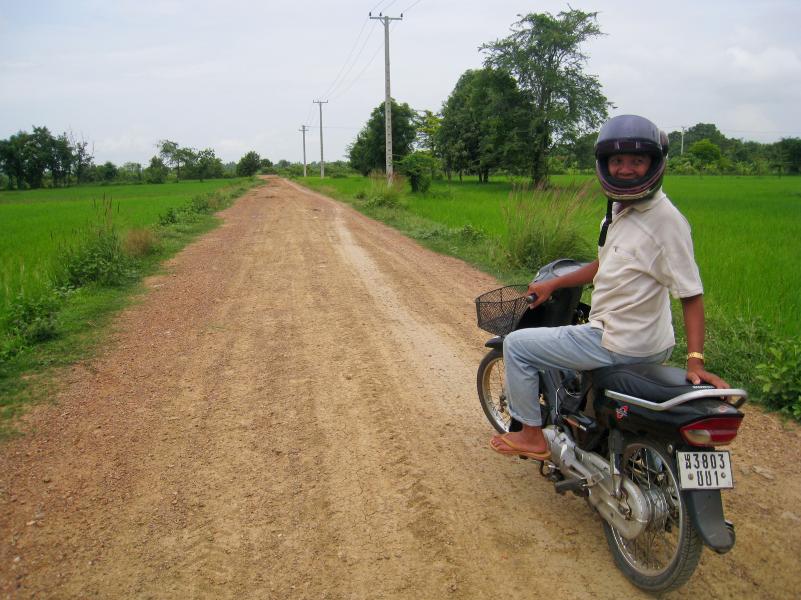 Phi-Lay, my Cambodian guide, on his motorbike outside Battambang