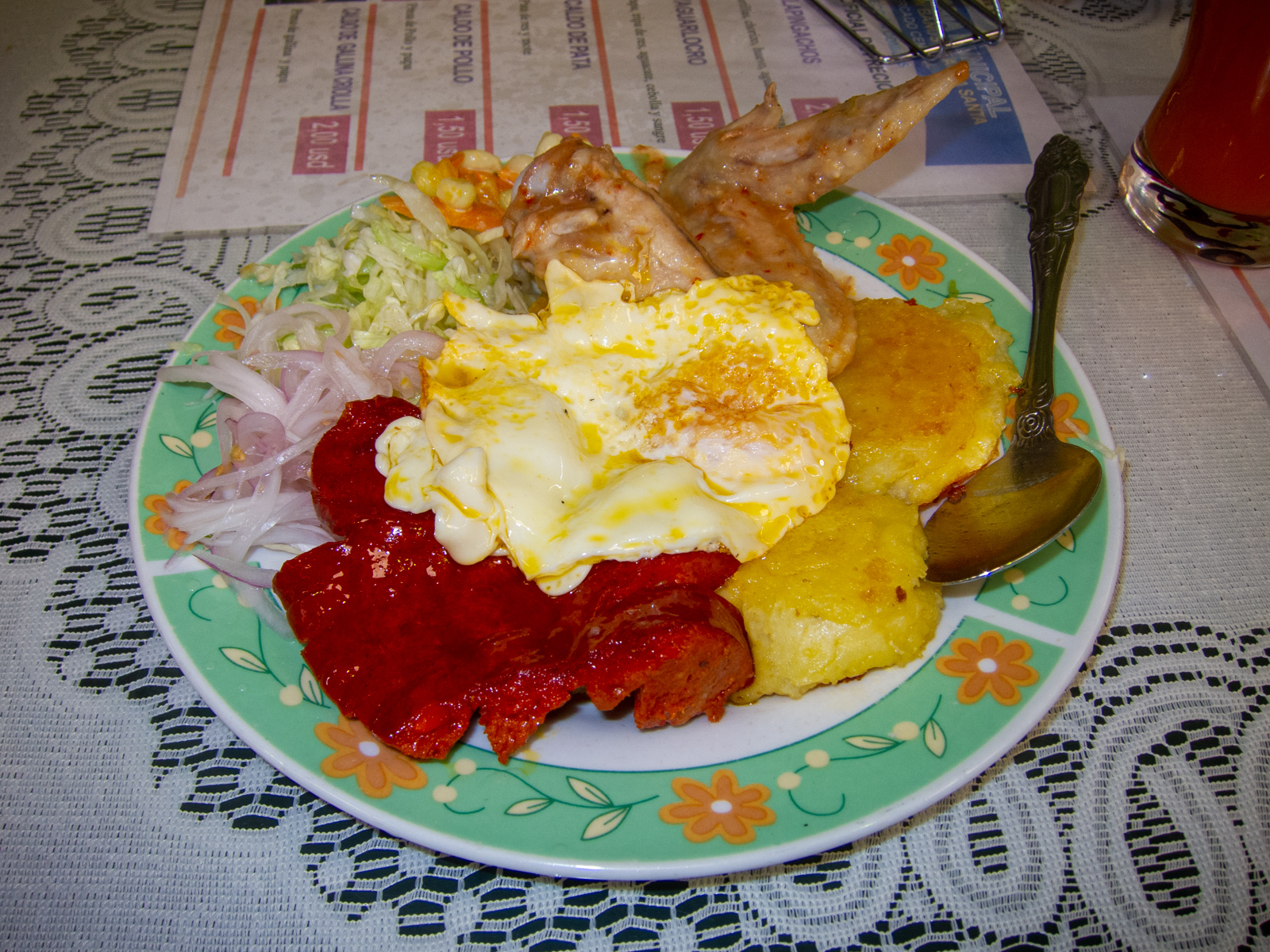 Llapingachos served with chicken, chorizo, a fried egg, and salad is typical of Ecuadorian food.